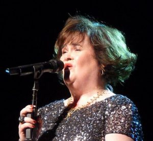 Susan Boyle singing in to mic, wearing black sequin dress.