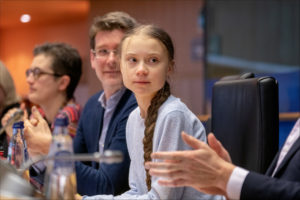Greta Thunberg sitting at a table with other people at European Parliament.